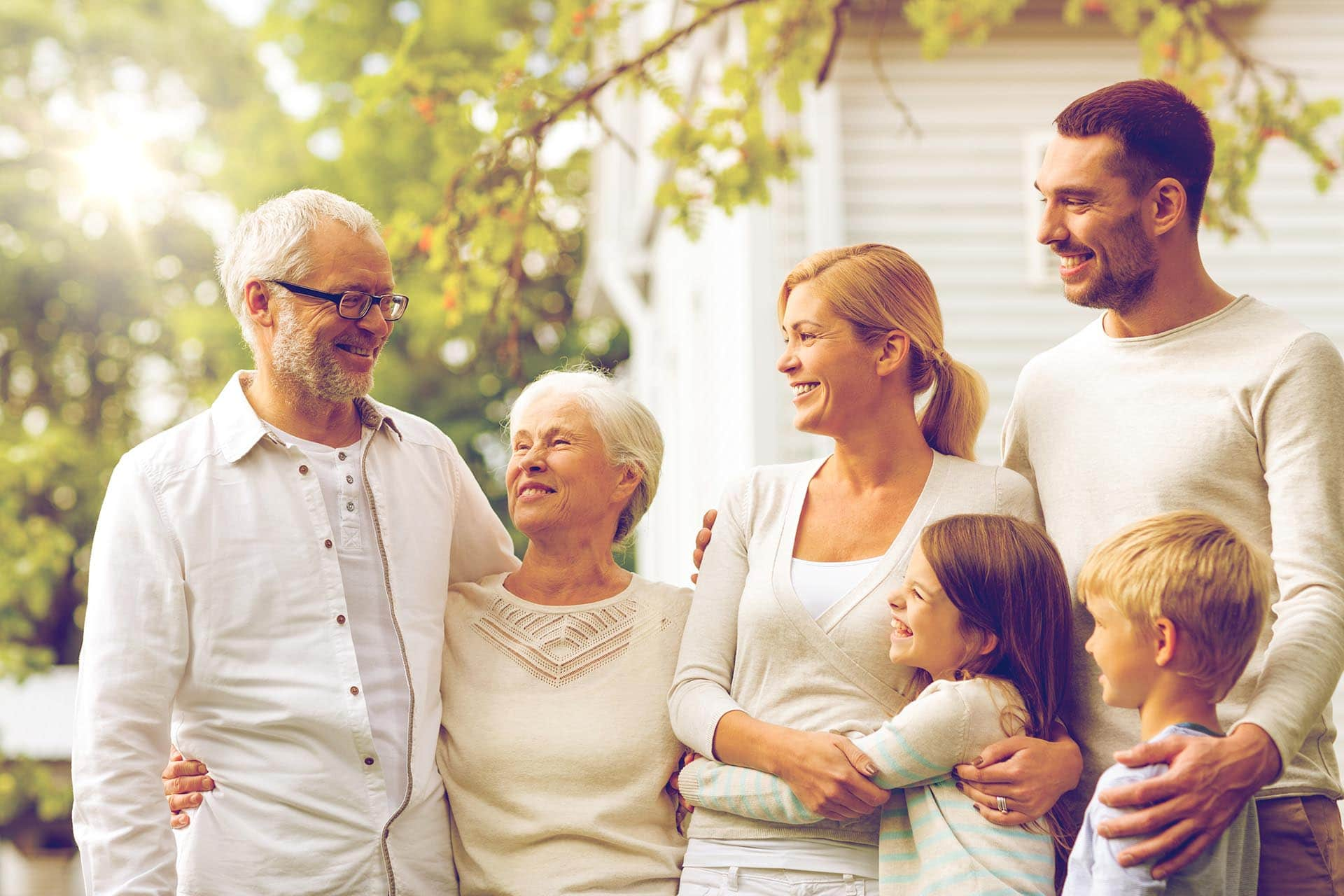 grandparents smiling with grandchildren in front of their house after choosing to get a reverse mortgage